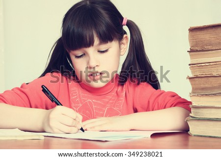 Little girl writes in a notebook on the background of a stack of old books. - stock photo