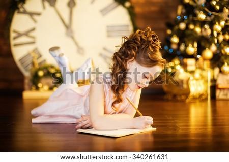 Little girl writes letter to Santa near christmas tree - stock photo