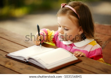 little girl writes to the notepad - stock photo