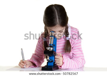 little girl writing and looking with microscope in school laboratory - stock photo