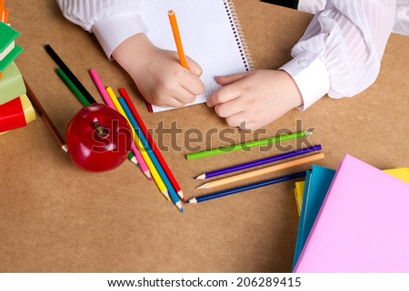 little girl writing in copybook, near lye red apple, many colorful books and pencils, top view  - stock photo