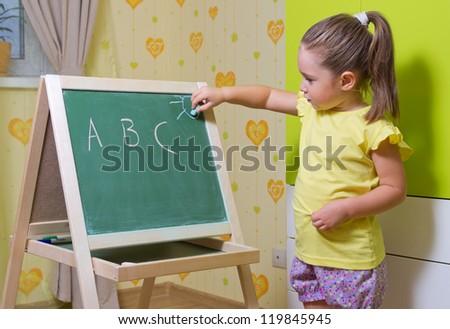 Little girl writing letters on blackboard - stock photo