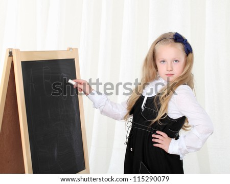 Little girl writing on black board by chalk and looking to camera - stock photo