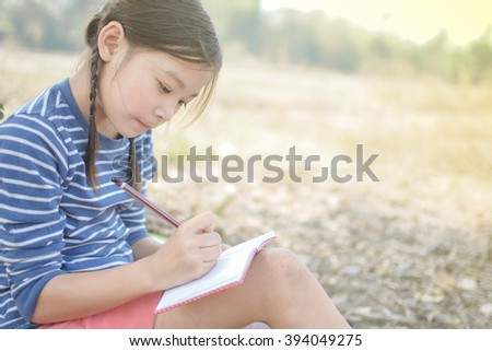 little girl writing on her notebook in the park,vintage tone soft focus - stock photo