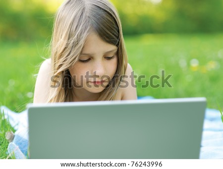 Little girl writing on notebook outdoor - stock photo