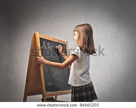 Little girl writing the alphabet on a blackboard - stock photo