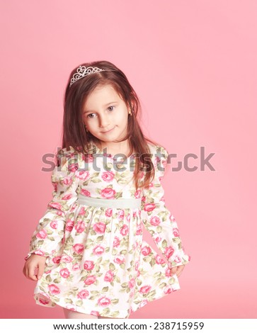 Little girl 4-5 year old posing in room over pink. Wearing trendy floral dress.  - stock photo