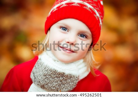 little girl 4 years old in a red hat and coat walking in autumn park in October, during the golden autumn with a bouquet of yellow maple leaves smiling