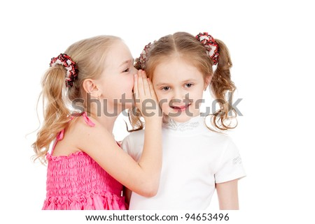 Little girlfriends sharing a secret isolated on a white background - stock photo