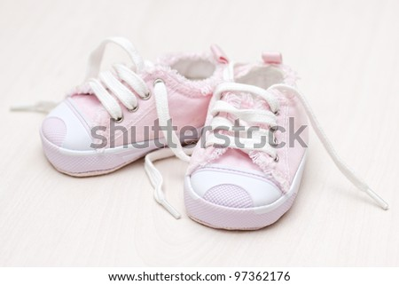 little girlie baby shoes on a wooden floor - stock photo