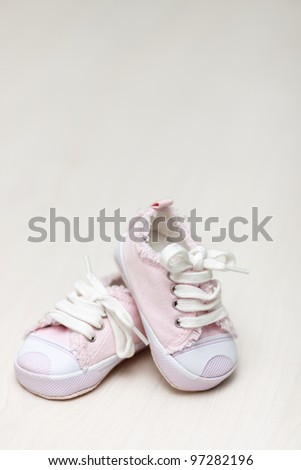 little girlie baby shoes on a wooden floor, copy space for text - stock photo