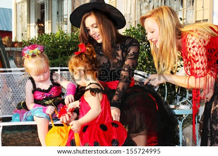 Little girls and their mothers check out candy after trick-or-treating - stock photo