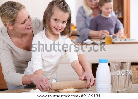 Little girls and their mums making cakes - stock photo