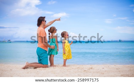 Little girls and young dad on white beach during summer vacation - stock photo