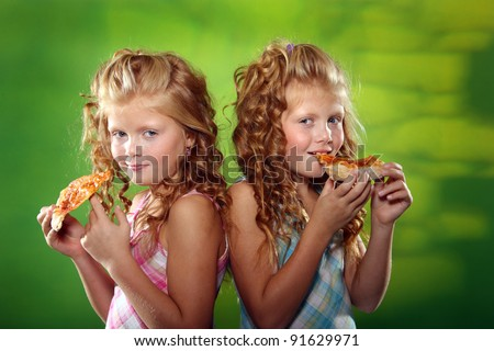 Little girls are eating pizza - stock photo