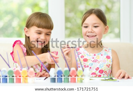 Little girls are painting with gouache while sitting at table