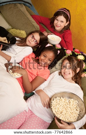 Little girls at a sleepover eat popcorn and tortilla chips - stock photo