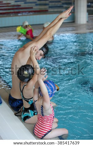little girls at swimming lesson in indoor swimming pool - stock photo