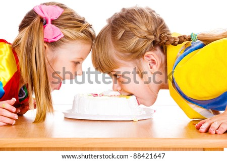 Little girls biting a cake - stock photo