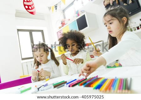 Little girls drawing and learning in the kindergarten - stock photo