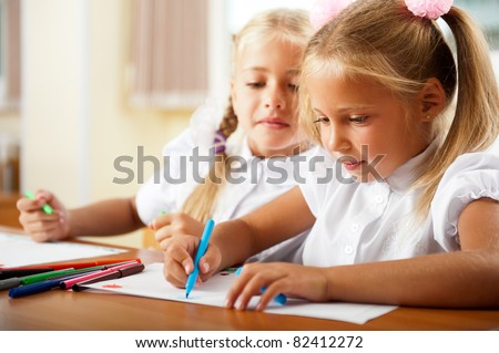 Little girls drawing pictures and writing letters to Santa Claus to get christmas gifts. Indoor at classroom