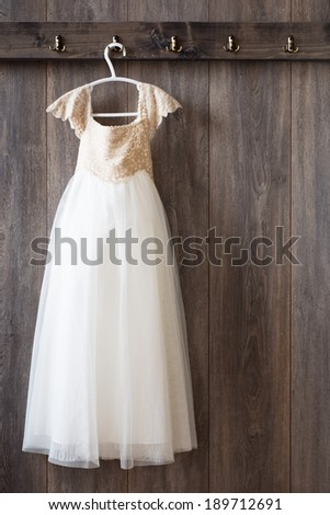 Little girls dress hanging from hook on wooden panelled wall - stock photo