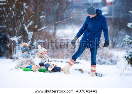 Little girls enjoy a sleigh ride. Father sledding his little adorable daughters. Family vacation on Christmas eve outdoors - stock photo