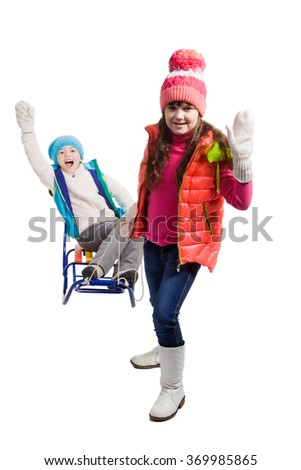 Little girls enjoying a sleigh ride. Child sledding. Sisters riding a sledge. Children play in snow. Outdoor winter fun for family Christmas vacation. - stock photo