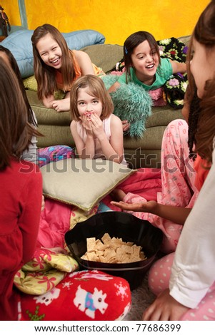 Little girls giggle and eat snacks at a sleepover - stock photo