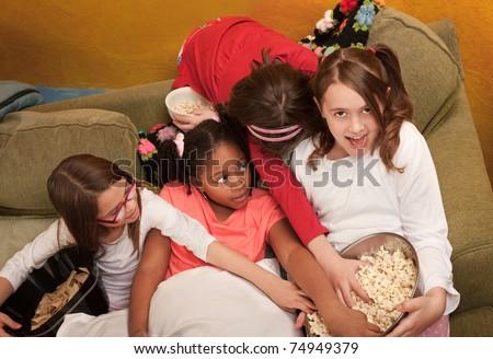 Little girls grab popcorn at a sleepover - stock photo