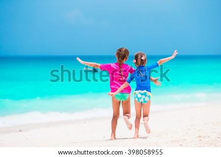 Little girls having fun at tropical beach during summer vacation playing together at shallow water - stock photo