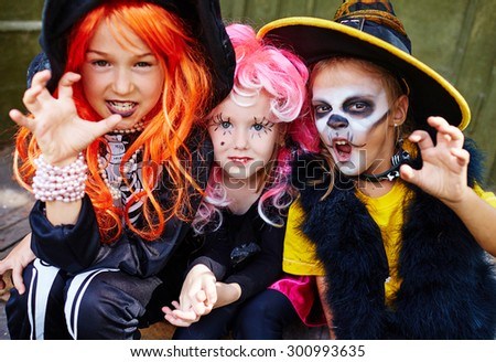 Little girls in Halloween costumes looking at camera with frightening expression - stock photo