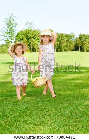 Little girls in straw hats carrying  fruit basket - stock photo
