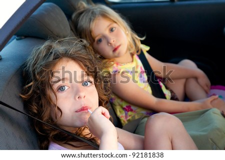 little girls inside car eating candy stick selective focus - stock photo