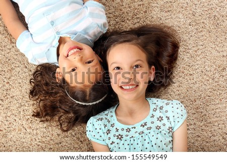 Little girls laying on the carpet - stock photo