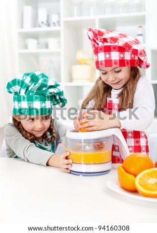 Little girls making fresh orange juice in the kitchen - healthy life education - stock photo