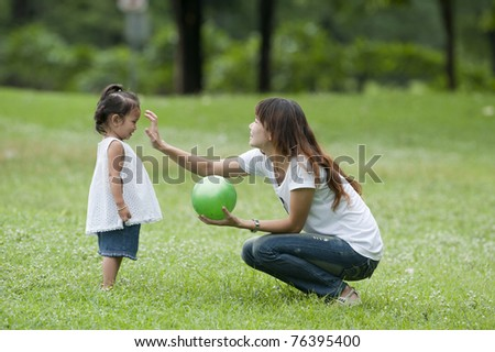 Little girls play ball on the grass with her mother.,mother day