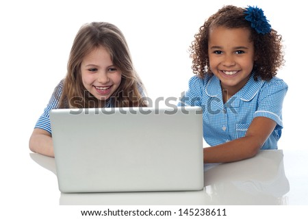 Little girls playing games on laptop - stock photo