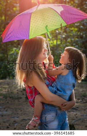 Little girls playing in a pine forest with color umbrella. a backlit - stock photo