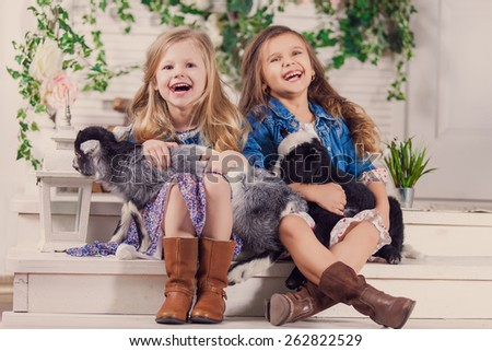 Little girls playing with a baby goat on a house porch - stock photo