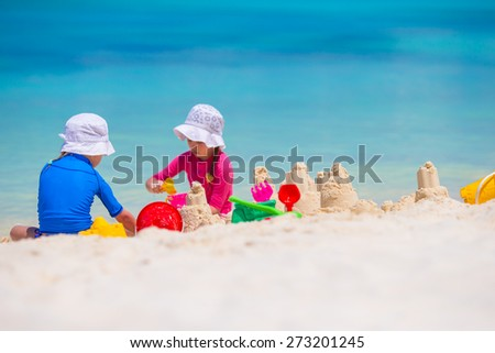 Little girls playing with beach toys during tropical vacation - stock photo