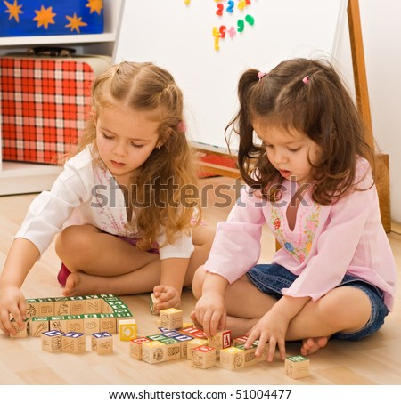 Little girls playing with blocks on the floor