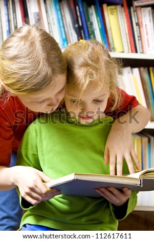 Little girls reading together near the bookshelf