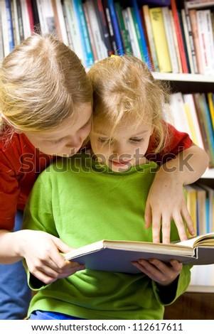 Little girls reading together near the bookshelf - stock photo