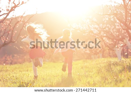 Little girls running on meadow with sunset