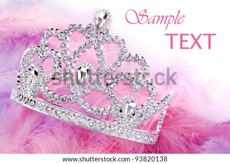 Little girls shiny tiara with pink and purple feathery boa on white background with copy space.  Macro with shallow dof to create dreamy effect.