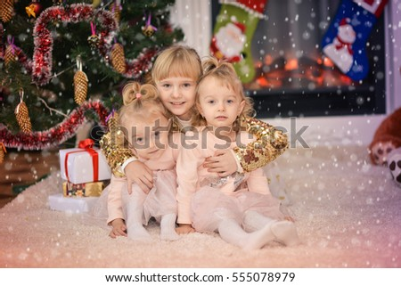 Little girls sisters with gifts near a Christmas tree.