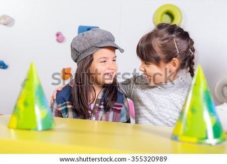 Little girls sitting and talking in the playroom