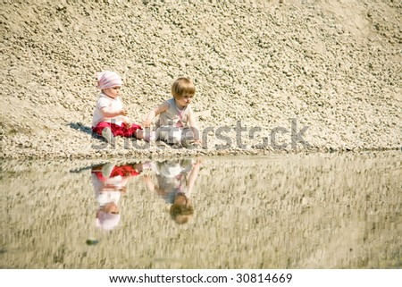 little girls sitting on a stones-beach near water - stock photo