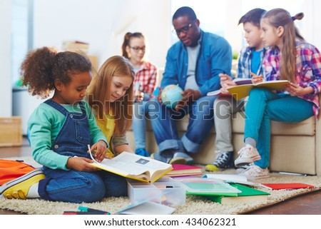 Little girls sitting on the floor and reading a book with other children studying in the background